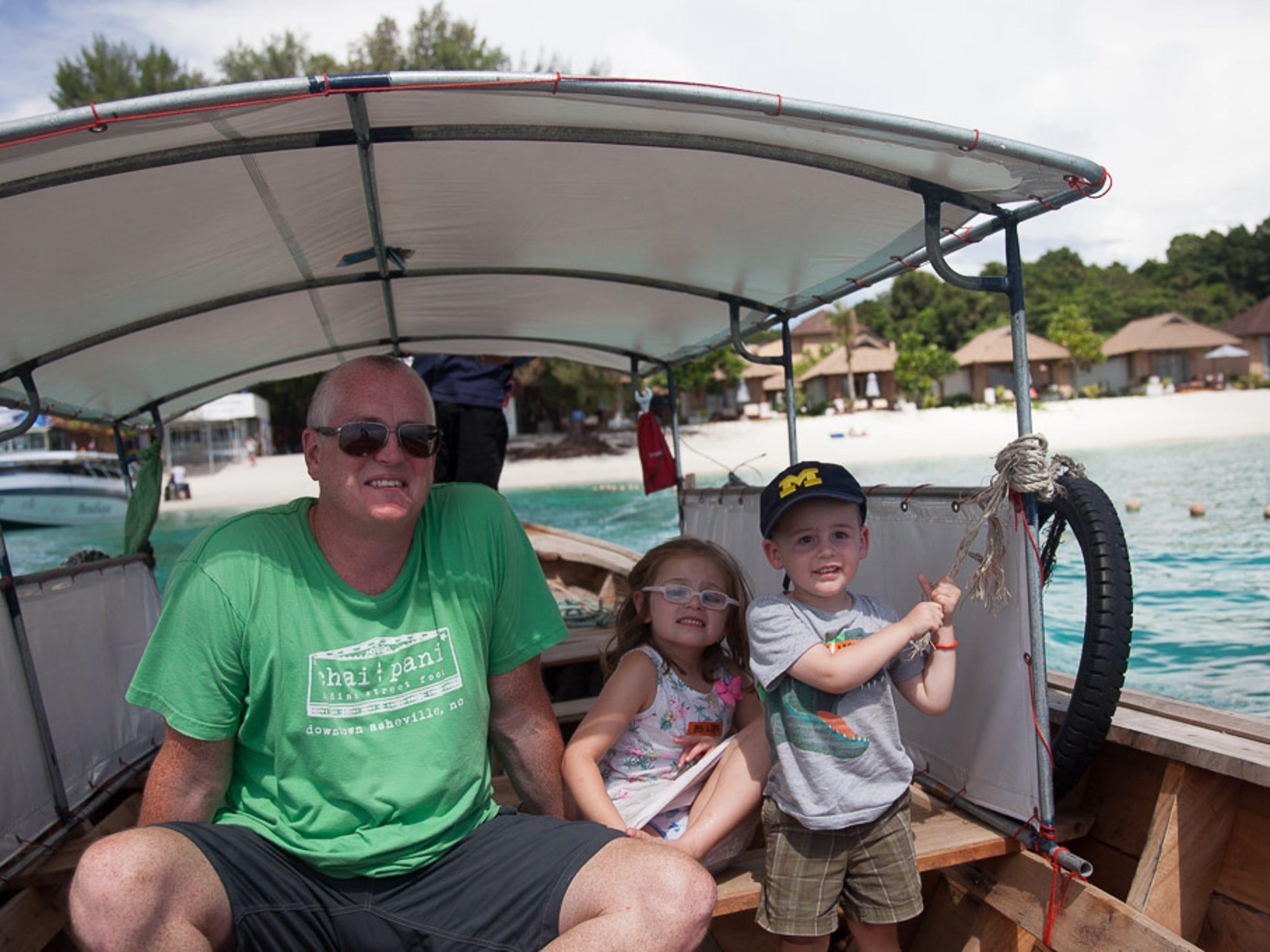 Derek, Harper and Walker Hughey on a longboat, the