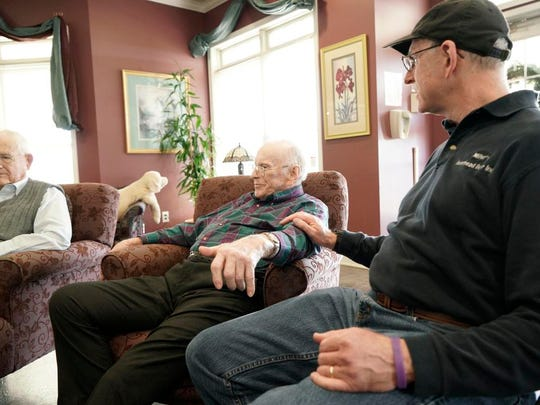Penny Wilson Sr., center, sits with his son, Penny Wilson Jr., while recalling the story of his surprise visit home at Christmas while serving in the South Pacific Ocean with the Navy's 85th Naval Construction Battalion.