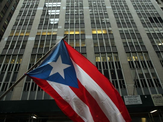 The Puerto Rican flag flies as people protest outside