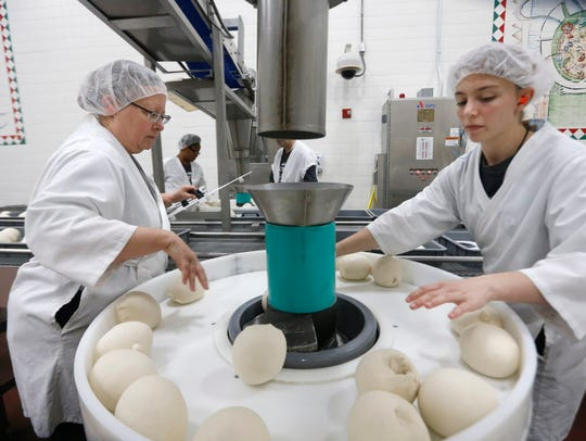 Workers in the production room at Papa John's Pizza