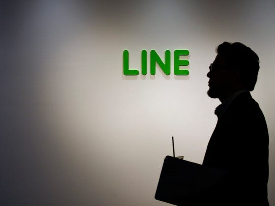 A man walks past Line Corp. company logo at the company's