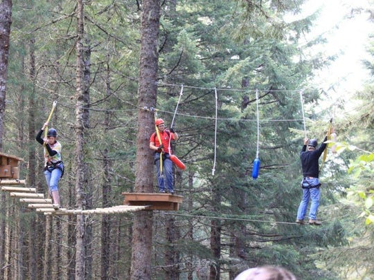 People are safely harnessed in and attached to cables