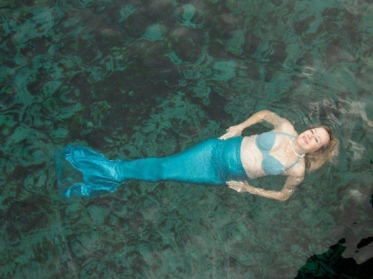 A photographer spends time in the water with the mermaid