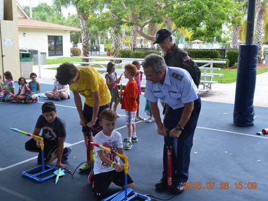 Members of the Marco Island Civil Air Patrol help Camp Mackle campers launch homemade paper rockets at a Aerospace Education and Rocketry workshop last month.