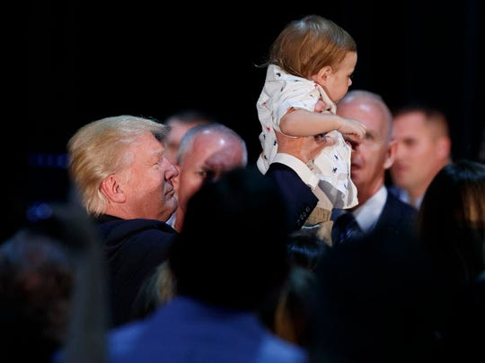 Republican presidential candidate Donald Trump lifts a child after delivering a policy speech on child care Sept. 13, 2016, in Aston, Pa.