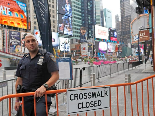A police officer stands guard at a section of Times