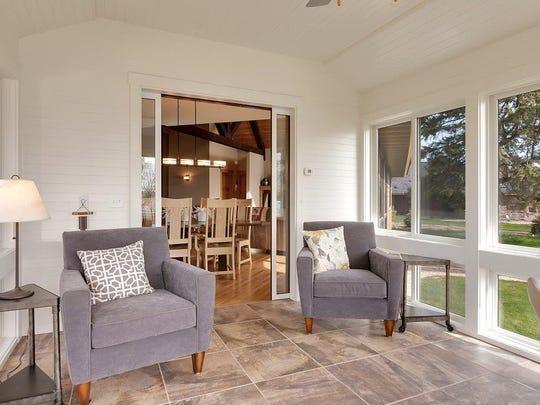 The heated sun room has three floor to ceiling windows.