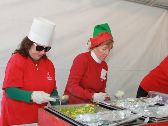 Volunteers serve food at a Holiday Express event.