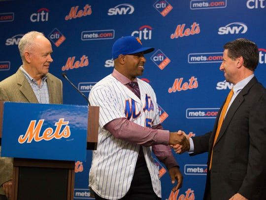 Yoenis Cespedes shakes hands with Jeff Wilpon while Sandy Alderson looks on at a press conference Wednesday.