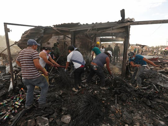Local residents comb through ashes and rubble at the