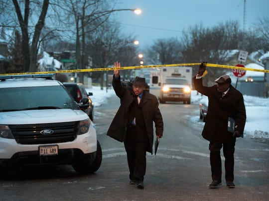 Police investigate the scene of a quadruple homicide