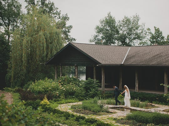 Kristi and Brendan Noonen of Chicago stroll through a Stout's Island Lodge garden, near Birchwood, before heading to their outdoor wedding reception on July 29, 2014.