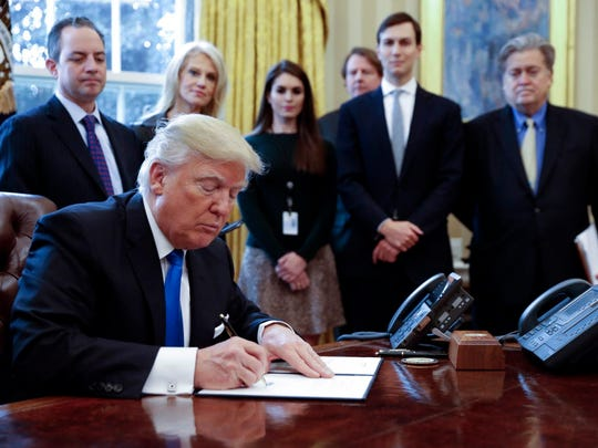 President Donald Trump signs executive orders  related to the oil pipeline industry in the Oval Office on Jan. 24, 2017.