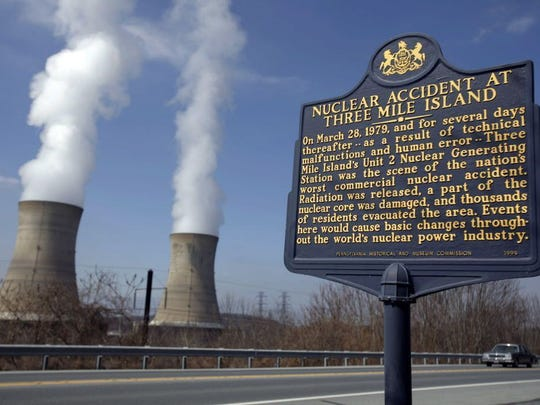 A historic marker is seen as the cooling towers of Three Mile Island's Unit 1 Nuclear Power Plant pour steam into the sky in Middletown, Pa., March 17, 2009. Three Mile Island's Unit 2 nuclear power plant was the scene of the nation's worst commercial nuclear accident on March 28, 1979.