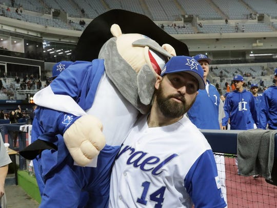 """March 8: Cody Decker of Team Israel holds the team mascot, """"The Mensch on the Bench,"""" after a 4-2 win over the Netherlands."""