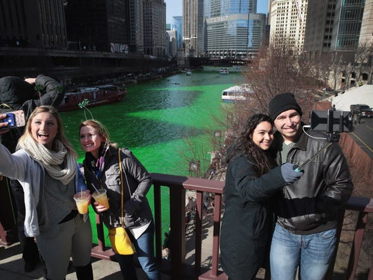 Visitors take selfies along the Chicago River shortly after it was dyed green in celebration of St. Patrick's Day on March 11, 2017, in Chicago. Dyeing the river has been a St. Patrick's Day tradition in the city since 1962.