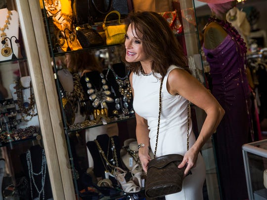 Co-owner of Audrey's, Quenby Tyler, helps customers in the consignment shop in Naples on Tuesday, March 14, 2017.