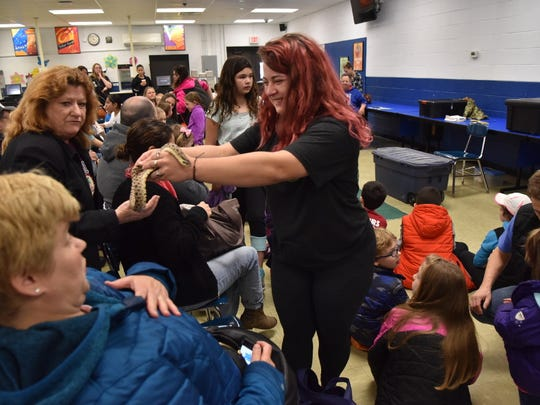 Samantha Slevant of Rizzo Reptiles showing a snake to Chloe Bakalian and her mother, Tania, at Hawthorne's Earth Day celebration.