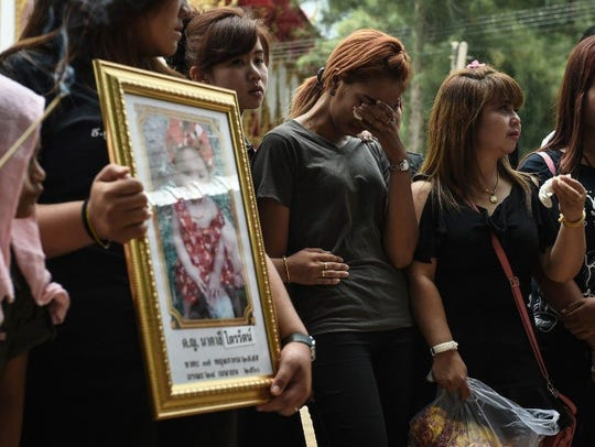 Tearful relatives gathered outside a Thai temple on