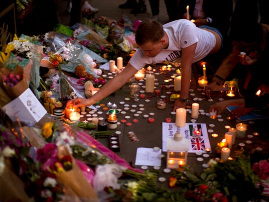 A man lights candles after a vigil in Albert Square,