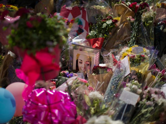A portrait of Eilidh MacLeod, 14, who has been named as one of those who died in Monday's Manchester bombing, is seen at St Ann's Square in central Manchester, England, Friday, May 26 2017. British police investigating the Manchester Arena bombing arrested a ninth man while continuing to search addresses associated with the bomber.