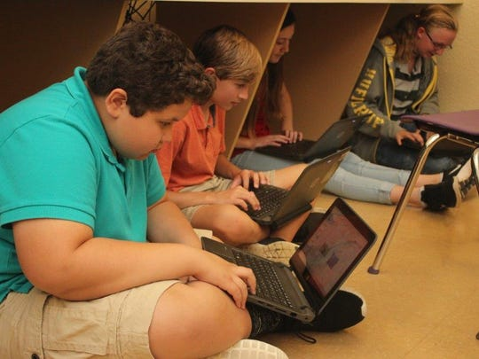 Martin County School District students William Jankens, Ryan Campbell, Emma Fariello and Lily Owens work on their laptops.