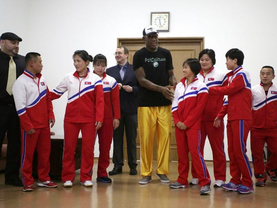 Former NBA basketball star Dennis Rodman, center, poses