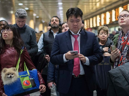 In this file photo, evening rush-hour commuters inspect the departures information board while they wait for their respective Long Island Rail Road trains at Penn Station in New York.