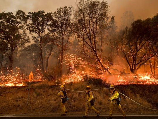 Firefighters battle a wildfire as it threatens to jump