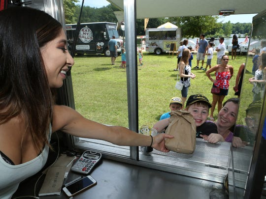Natalia Lopez, (left) of The Empanada Times food truck, hands over fresh made empanadas to 5-year-old Aaron and his mother, Amy Redner at the Food Truck Festival.