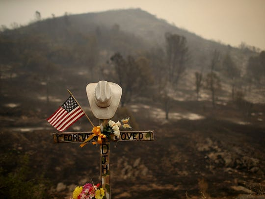 A roadside memorial stands next to an area burned by