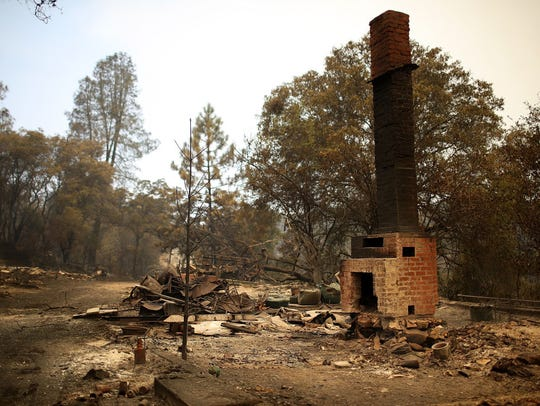A chimney stands in the remains of a home burned by