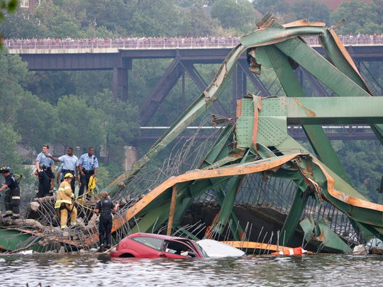 In this Aug. 1, 2007 file photo, emergency personnel work at the scene where the Interstate 35W bridge collapsed over the Mississippi River in Minneapolis. Tuesday, Aug. 1, 2017 marks the ten-year anniversary of the disaster killed 13 people and injured 145.