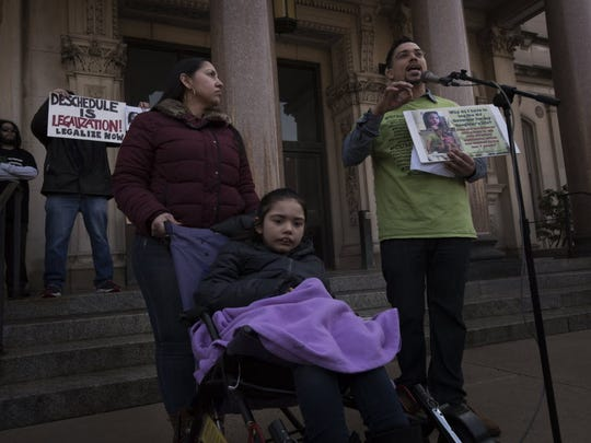 "TRENTON, NJ 03/21/2015 Groups advocating for marijuana legalization in New Jersey demonstrate outside the Statehouse in Trenton. (from - right) Ricardo Rivera, an Army veteran from Oaklyn, speaks during the rally as his wife Jenny looks on. (lower - left) His daughter Tatyana, 8, nicknamed ""Tuffy"", has a severe form of epilepsy called Lennox-Gastaut syndrome. She was having up to 30 violent seizures a day, but since she has been taking cannabis she now can go several weeks without having a seizure. She needs an edible form of medical marijuana, but since none are available for sale in New Jersey Ricardo is forced to make it himself and he is unable to accurately control the dosage. He believes that if his daughter had access to a controlled and consistent dosage her condition would further improve. A new bill introduced by Cory Booker, Rand Paul and Kirsten Gillibrand would legalize medical marijuana under federal law and would make it legal to have edible forms shipped to NJ from out of state. The ""NJ Spring Smoke-Out"" rally supports the legalization of marijuana but also ""any progressive measures on marijuana,"" according to a Facebook page for the event. Supporters marched from the NJ Transit River Line Station to the Statehouse. Advocates spoke at the demonstration and at 4:20pm a large group of people smoked marijuana across the street from the Satehouse."