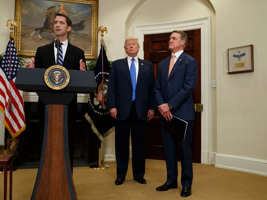 President Donald Trump, center, and Sen. David Perdue, R-Ga., right, listen as Sen. Tom Cotton, R- Ark. speaks in the Roosevelt Room of the White House in Washington in August during the unveiling of legislation that would place new limits on legal immigration.