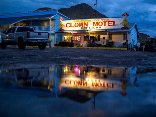 The office of the Clown Motel is reflected in a puddle