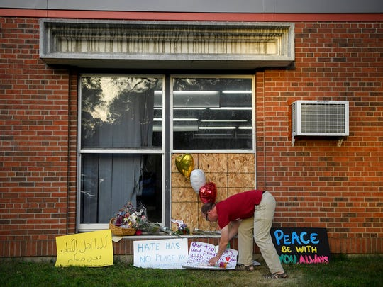 A man places a sign of support near a window damaged during the Aug. 5, 2017 attack at the Dar Al-Farooq Islamic Center in Bloomington.