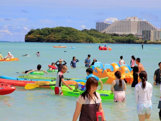 Tourists enjoy the activities along Tumon beach on