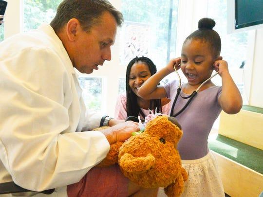 Dr. Scott Henning offers the stethoscope to Katasha