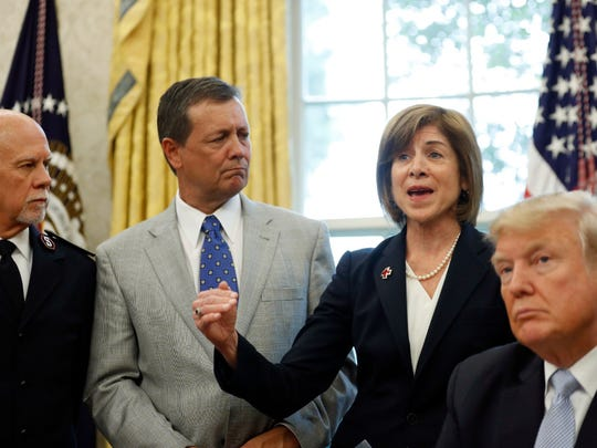 President Donald Trump listens, along with Commissioner