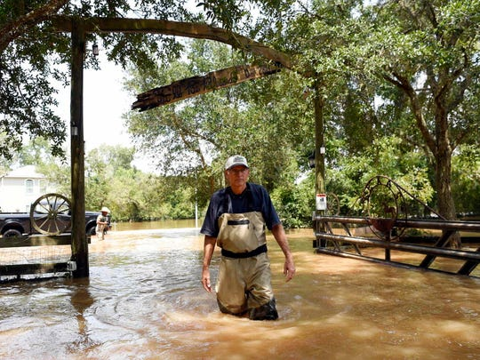 Tom Powell walks onto his flooded Trinity Oak Creek