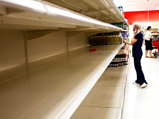 Kailey Coventry walks past empty shelves of water at