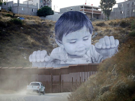 A Border Patrol vehicle drives in front of an art installation