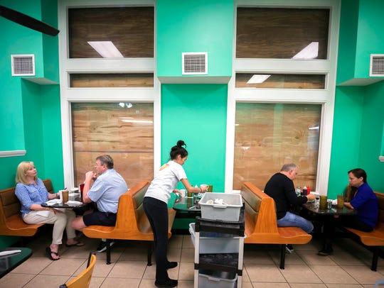 Henry's Restaurant manager Nhi Brayman, center, cleans