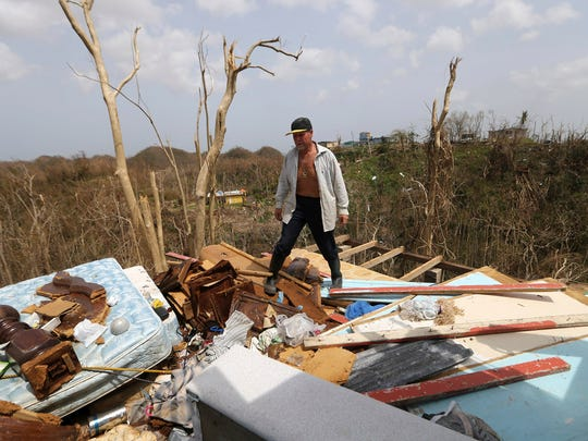 Jose Trinidad walks on what is left of his home in Montebello, Puerto Rico, on Tuesday in the aftermath of Hurricane Maria.