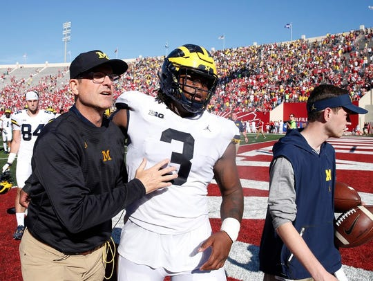 Michigan Wolverines coach Jim Harbaugh walks off the
