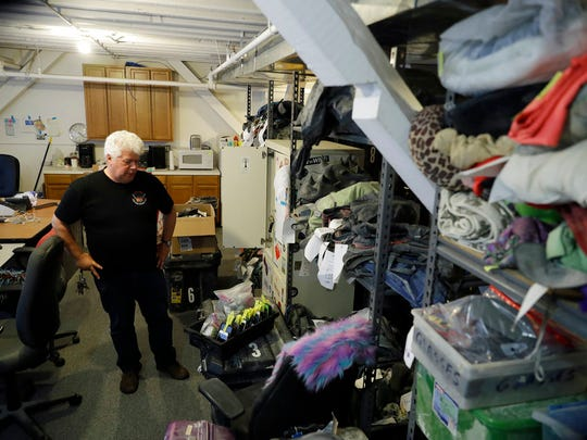 In this Tuesday, Nov. 21, 2017 photo, Terry Schoop, community services department manager for Burning Man festival, looks through some lost and found items at the organization's headquarters in San Francisco.