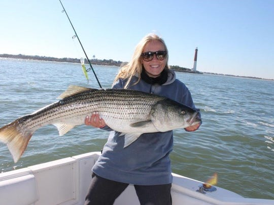 Kristen Ahrens, Lanoka Harbor, holds a 35-pound striped bass she caught Nov. 24, 2017 off Island Beach State Park.