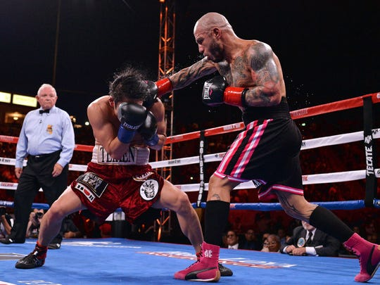 Miguel Cotto, right, connects with a right hand against Yoshihiro Kamegai in August.