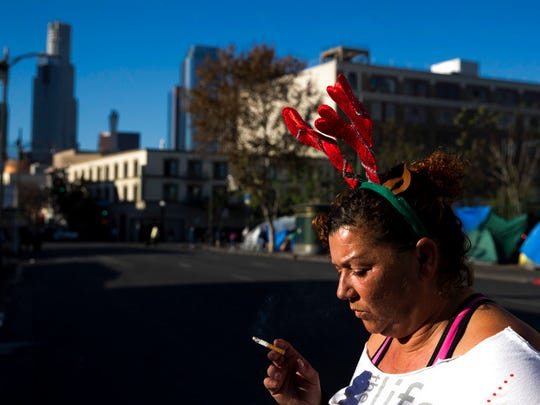 Wearing a Christmas headband, Grace Fernandez, who is homeless, smokes outside her tent in the Skid Row area of downtown Los Angeles, Friday, Dec. 1, 2017.